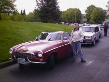"My lovely wife Heather next to a P 1800 S, it is now her favorite ""Old"" car.  The building just off her left shoulder is IPd, you can see all the Volvos parked on NE Ainsworth Cir."
